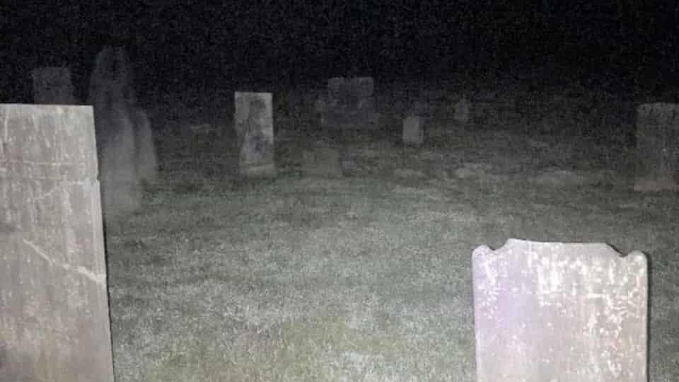 Imagem arrepiante mostra 'Fantasma' espreitando sobre túmulo de cemitério mundo sombrio